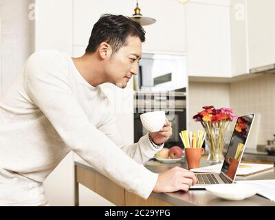 young asian businessman working from home standing by kitchen counter holding a cup of coffee looking at laptop computer