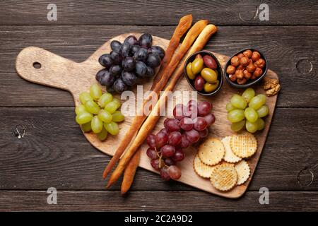 Grapes, nuts, bread sticks and olives antipasto. Appetizer selection on wooden board. Top view. Flat lay - Stock Photo
