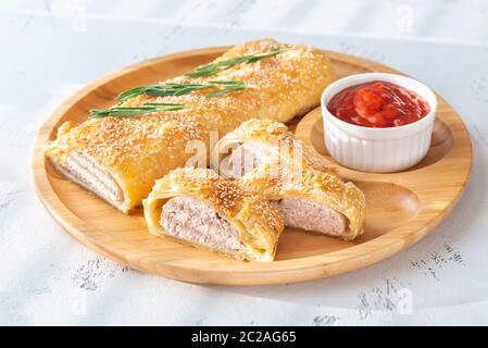 Sausage rolls with tomato sauce on the wooden tray