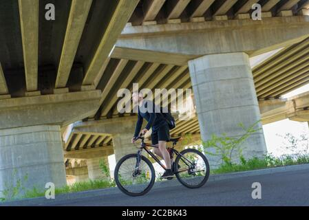 Cyclist riding a bike on an open road to the sunset athlete, bearded guy cyclist, rides on the highway on a sports bike. Under the bridge. Outdoors. S