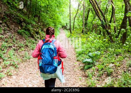 Hiking, Travel, Healthy Lifestyle.Active woman with backpack walking on a rural road in autumn day.