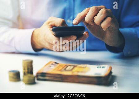 fintech concept - businessman using smart phone to make financial transactions - Stock Photo