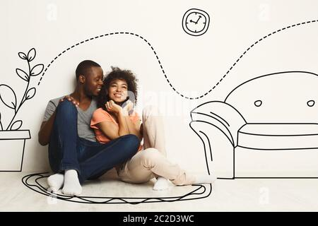 Black guy and his girlfriend imagining new furnished home against white wall with interior drawings - Stock Photo
