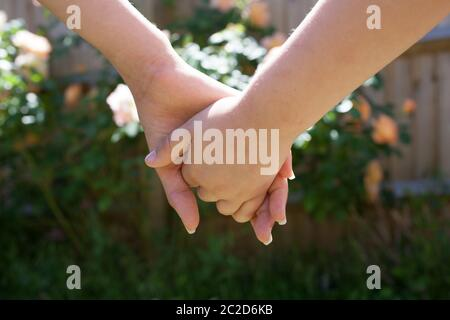 Two children's hands holding together with flowers in the background - Stock Photo