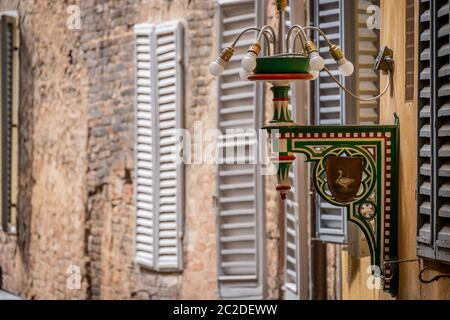 Siena, Italy, April 2018: Street Lamp of the goose district in Siena. Tuscany, Italy. Each colour and shape marks one specific territory which belongs to one specific Contrada. High quality photo