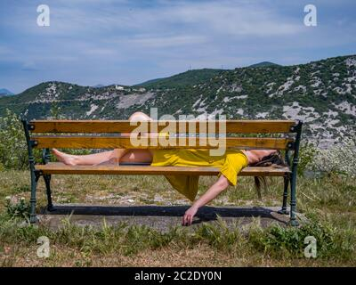 Teengirl resting relaxing tired on park bench sideview side-view - Stock Photo