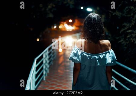 Young lonely woman walking on the bridge at night - Stock Photo