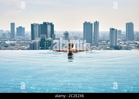 Young man relax on the edge of swimming pool in roof top of hotel - Stock Photo