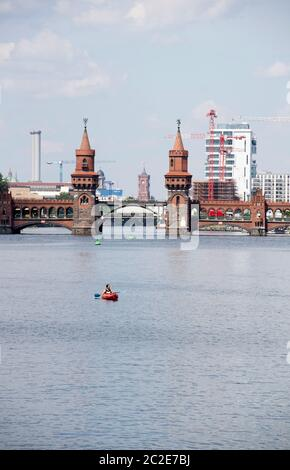 Berlin, Germany. 17th June, 2020. A canoeist lets himself be carried away by the waves on the Spree in front of the Oberbaumbrücke. Credit: Paul Zinken/dpa/Alamy Live News - Stock Photo