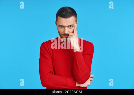 Young thoughtful man thinking and looking to camera with copy space, isolated on blue background Stock Photo