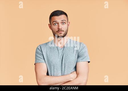 Surprised and shocked young man with crossed arms looking to camera over beige background