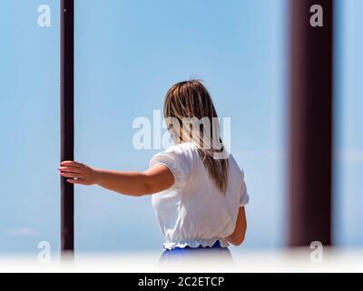 Teengirl hand holding metal post column looking away rearview - Stock Photo