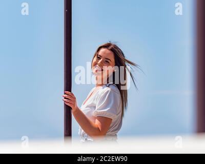 Teengirl spontaneous with teeth braces looking at camera ey eyes contact eyeshot hand holding metal post column - Stock Photo