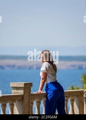 Teengirl standing by fence overlooking sea seaside looking away watching on watch - Stock Photo