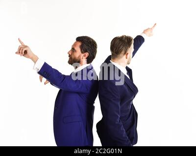 Young businessmen pointing in two different directions at same time. Handsome guys nice suits on white background, isolated. - Stock Photo
