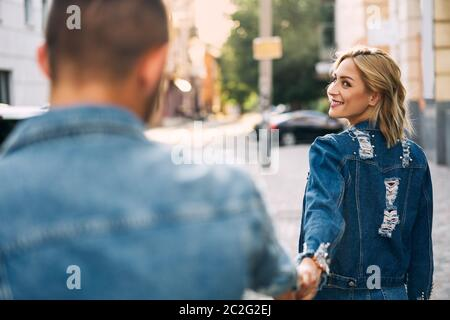 Beautiful young woman walking on the street and holding man by hand