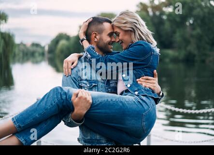 Happy couple enjoy each other on nature. Man holding woman on hands