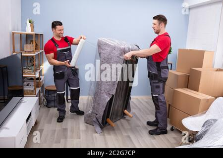 Two Young Male Movers Wrapping The Sofa With Plastic Wrap In Living Room - Stock Photo