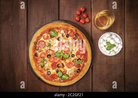 Pepperoni pizza with wine, tomatoes, Mozzarella cheese and basil, shot from the top on a dark rustic background with a place for - Stock Photo