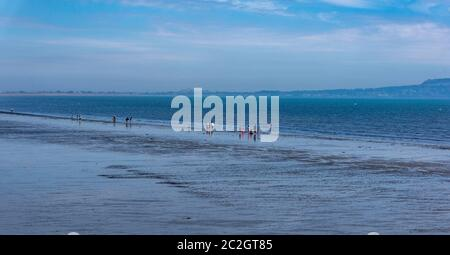 People gathered at the waters edge at Dollymount beach in Dublin, Ireland. - Stock Photo
