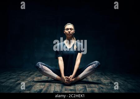 Young woman practicing yoga doing cobbler's pose on dark room - Stock Photo