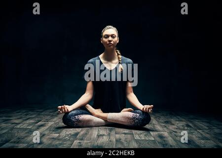 Young attractive woman practicing yoga sitting in lotus pose and meditating in dark room