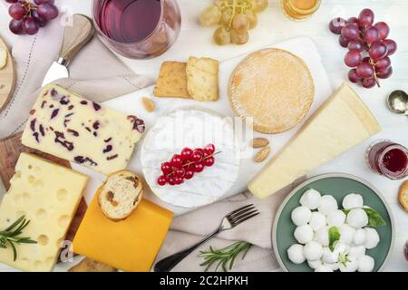 Wine and cheese platter, tasting and pairing. An assortment of various types of cheese and a glass of wine, shot from the top - Stock Photo