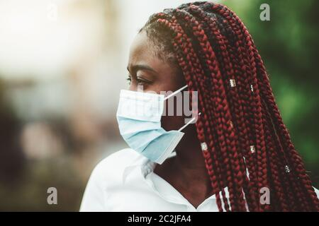 Close-up portrait of a young African woman with chestnut braids and in a virus protective mask over her face; masked black woman outdoors - protection - Stock Photo