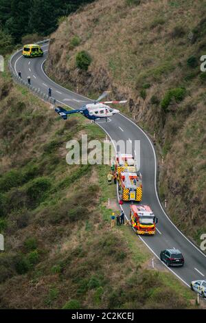 A MB BK117 / H145 rescue helicopter takes off from a road on the side of a mountain next to emergency service vehicles - Stock Photo