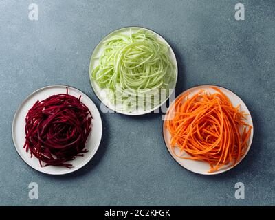 Vegetable noodles - zucchini, carrot, and beetroot noodles on plate over gray stone background. Clean eating, raw vegetarian, food concept. Copy space - Stock Photo