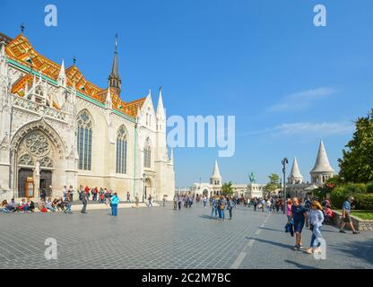 Tourists visit the Matthias Church square with the Fisherman's Bastion behind at the Buda Castle Complex in Budapest, Hungary - Stock Photo