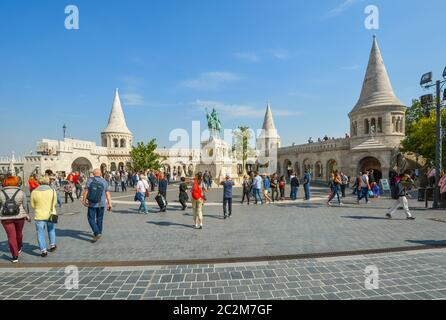 Tourists visit the Matthias Church square with the Fisherman's Bastion and statue of Saint Stephen I at the Buda Castle Complex in Budapest, Hungary - Stock Photo