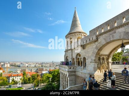 Tourists enjoy the fairy tale towers at Fisherman's Bastion overlooking the Danube River at Budapest Hungary's Castle Hill on a sunny day in autumn - Stock Photo