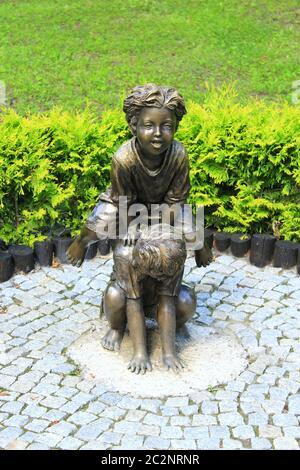 Bronze sculpture of children playing leapfrog in summer park