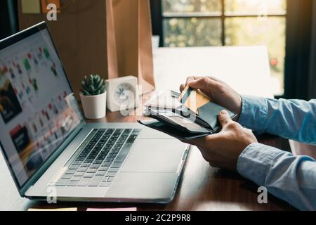Asian man hand is pulling a credit card out of his pocket in order to complete online shopping on the computer.