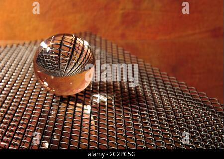Metal grid reflected in clear lensball.  Glass ball lying on top of grid agains orange background. - Stock Photo