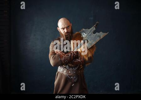 Viking with axe dressed in traditional nordic clothes. Ancient warrior. - Stock Photo