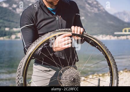Bike Repair. Man Repairing Mountain Bike. Cyclist man in trouble rear wheel wheel case of accident. Man Fixes Bike near lake in