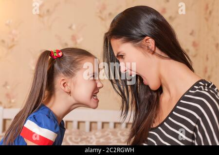 Young mother and her little daughter make each other terrible faces - Stock Photo