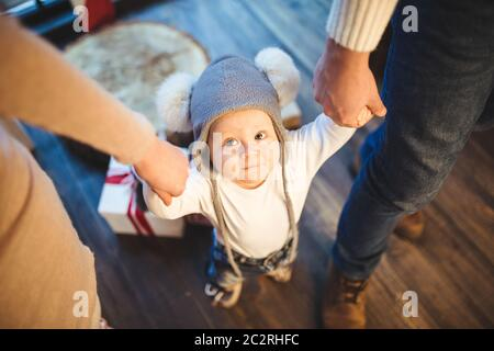 Funny little baby boy 1 year old learning walk home in winter in a decorated New Year house. Young family dad and mom hold by th