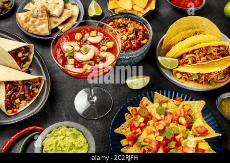 Mexican food, many dishes of the cuisine of Mexico on a black background. Shrimp cocktail, burritos, tacos, quesadillas, nachos, - Stock Photo