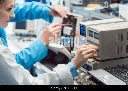 Two electronic engineers on the lab test bench measuring a new product for EMC compliance - Stock Photo