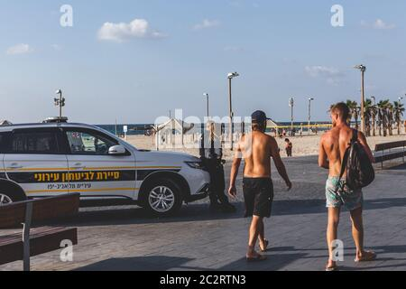 Tel Aviv/Israel-10/10/18: tourists walking past a police vehicle and two police officers on duty on the promenade in Tel Aviv - Stock Photo