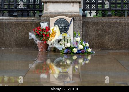 Westminster, London, UK. 18th Jun, 2020. The morning has dawned wet during the COVID19 Coronavirus pandemic lockdown period. The memorial to PC Keith Palmer which has flowers, tributes laid beside it