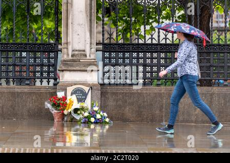 Westminster, London, UK. 18th Jun, 2020. The morning has dawned wet as commuters make their way to work during the COVID19 Coronavirus pandemic lockdown period. Some are passing the memorial to PC Keith Palmer which has flowers, tributes laid beside it