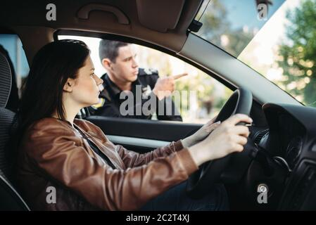 Male cop in uniform shows the way to female driver. Law protection, car traffic inspector, safety control job - Stock Photo