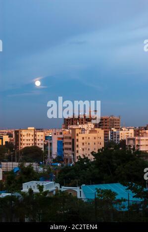 A full moon rising over the city of Hyderabad, Telangana, India.