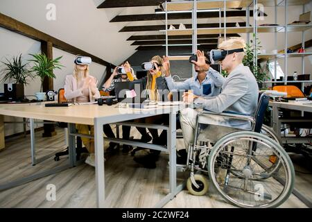 Meeting of skilled multiethnical young colleagues, sitting at the table and working together in office using vr goggles. Handsome disabled man in - Stock Photo