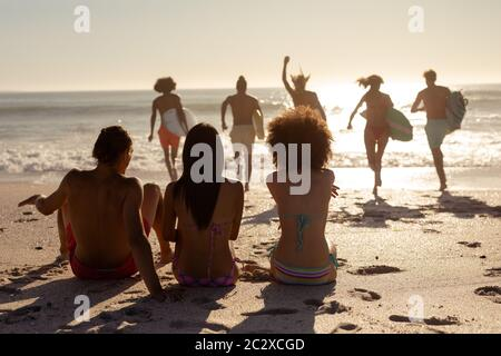 Multi-ethnic group of male and female, surfing on the beach - Stock Photo