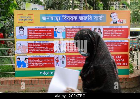 Dhaka, Bangladesh. 18th June, 2020. A woman passes a poster carrying messages on symptoms and awareness of coronavirus disease inside hospital premises in Dhaka, Bangladesh, June 18, 2020. Credit: Suvra Kanti Das/ZUMA Wire/Alamy Live News - Stock Photo